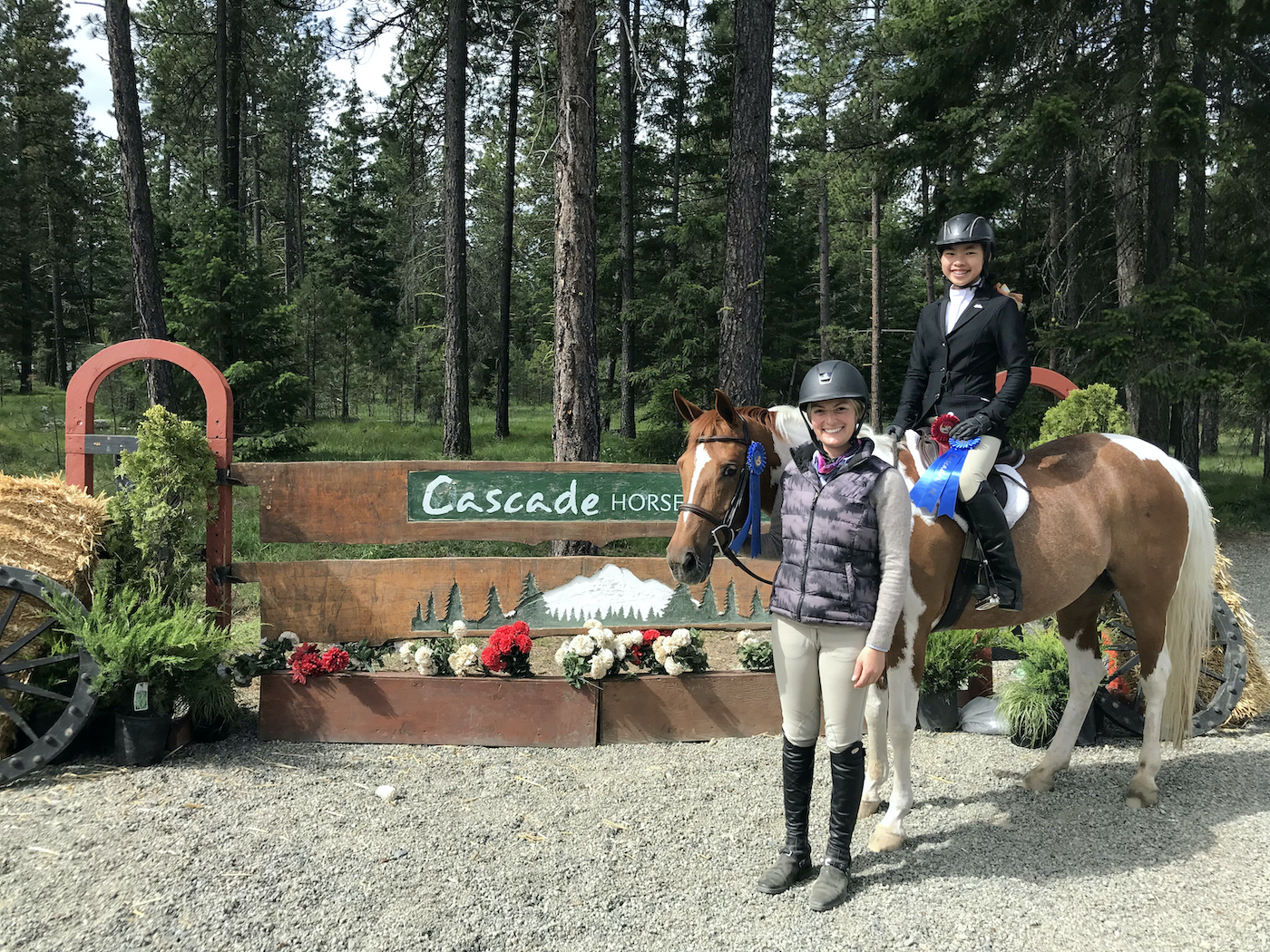 Jacque and Magnolia Ridge rider atop a horse pose with an award ribbon