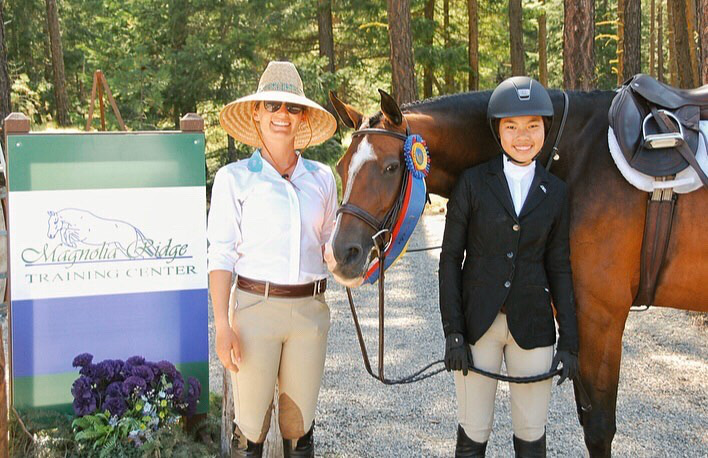Jacque poses with a Magnolia Ridge rider and her horse with a ribbon